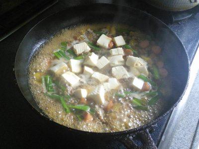 材料を炒め、調味料を入れ豆腐投入